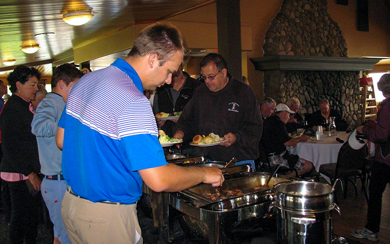 Group of individuals scooping food onto their plates at an even at the North Shore Grille at Bemidji Town and Country Club