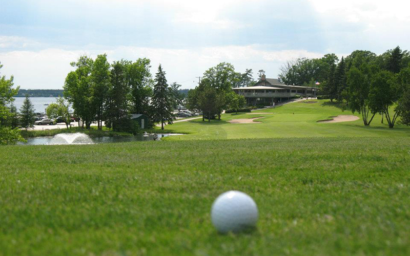 Golf ball out of focus in the foreground with Bemidji Town and Country Club in the background