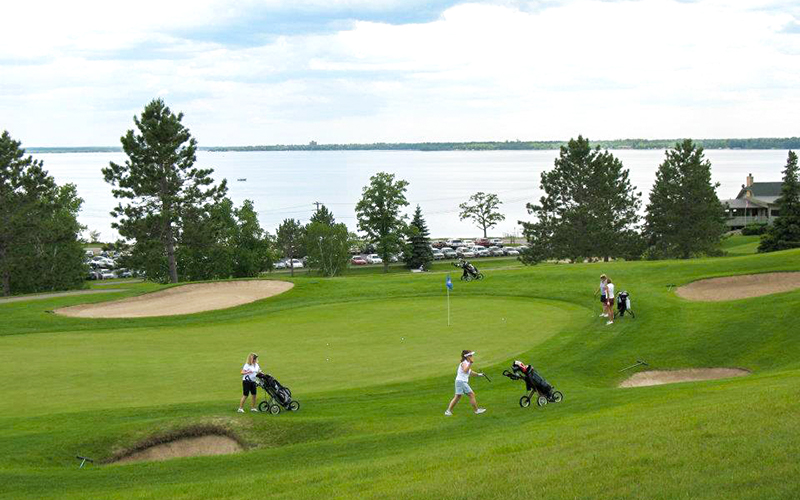 4 ladies getting ready to putt their ball into the hole at Bemidji Town and Country Club