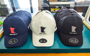 Blue, white, and black golf hats in the pro shop of Bemidji Town and Country Club