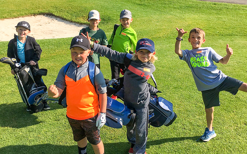 Junior golfers smiling for a photo while practicing at Bemidji Town and Country Club